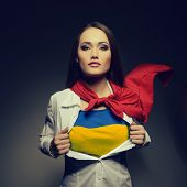 Pretty woman opening her shirt painted in ukrainian flag colors like superhero. Young girl twenty-ye