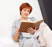 stock photo of only mature adults  - Adult woman reading book at sofa - JPG