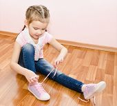 Cute Little Girl Tying Her Shoes