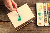 Hand of artist painting watercolor artwork