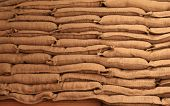 stock photo of sandbag  - Neatly stacked burlap sandbags on long wood table - JPG