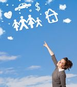 Young girl daydreaming with family and household clouds on blue sky