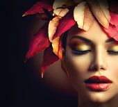 Fantasy Autumn Woman Fashion Portrait. Fall. Beautiful Model Girl face with colourful autumn leaves hairstyle over dark background. Fashion border Art design over black with copyspace for your text