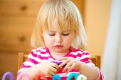 Little girl playing with plasticine at home