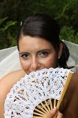 Young brunette bride posing holding a white fan