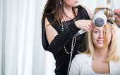 Hairdresser/Hairstyle artist working on a young woman's hair, giving it shape and volume