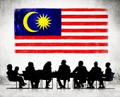Silhouettes of Business People and a Flag of Malaysia