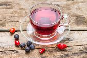 Glass Cup Of Red Karkade Tea With Wild Berries On Wood Background