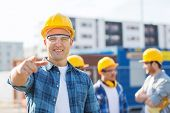 business, building, teamwork, gesture and people concept - group of smiling builders in hardhats poi