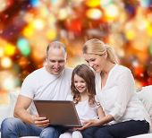 family, childhood, holidays, technology and people concept - smiling family with laptop computer over red lights background
