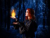 stock photo of moonlight  - Young witch at night in the moonlight forest with flame - JPG