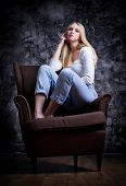 Young girl sit on the chair on grey wall background