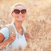 foto of fall-wheat  - Happy traveler girl sitting with backpack in wheat field - JPG