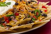 stock photo of shredded cheese  - Mexican nachos with sour cream black olives ground beef black beans tomatoes shredded cheese jalapenos rice and cilantro