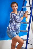Beautiful young woman doing wall painting, standing on ladder