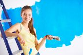 Beautiful young woman doing wall painting, sitting on ladder