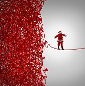 stock photo of debt free  - Santa Claus freedom and holiday management gift giving crisis as a concept with santaclause as a tightrope walker walking out of a confused tangled chaos of red ribbons breaking free to a clear as a metaphor for managing and escaping Christmas stress - JPG