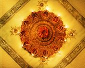 foto of pooja  - A lit up decorative earthen indian lamp placed on a luxurious fabric - JPG