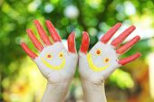 Smiling colorful hands on natural background