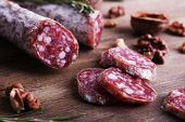 French salami and walnuts on wooden background