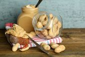 Beautiful still life with fresh peanut butter on wooden background