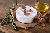 Camembert cheese on paper, honey in glass bowl and nuts on cutting board on wooden background
