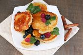 Tasty pancakes with fresh berries, honey and mint leaf on plate, on  wooden background