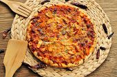 a pizza with chicken, red pepper and green pepper, served on a wooden background