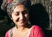 Smiling Pretty Young Woman Leaning at Tree Looking Down. Outdoor Capture.