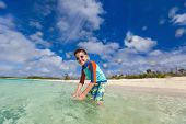 Happy boy playing at shallow water at tropical beach