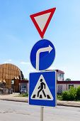 Triangular, Round And Square Traffic Signs Above Blue Sky