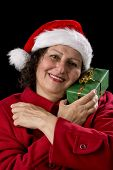 Happy Aged Woman With Santa Cap And Wrapped Gift.