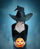 picture of horror  - Mystery witch holds Halloween pumpkin on dark background - JPG