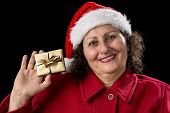 Smiling Old Lady Shows Golden Wrapped Christmas Gift.