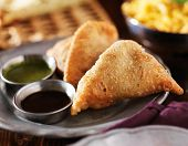 plate of indian samosa with mint and hot chutney