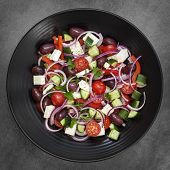 Greek salad on black plate over dark slate.  Overhead view.