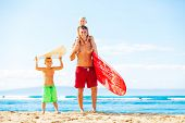 Father and Young Sons Going Surfing at the Beach