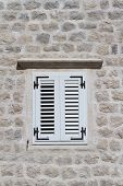Shuttered Window In A Stone Wall Of A House Close-up