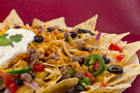 stock photo of jalapeno  - Mexican nachos with sour cream black olives ground beef black beans tomatoes shredded cheese jalapenos rice and cilantro