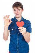Handsome young man in denim blue shirt standing on a white background with a red paper heart in hand