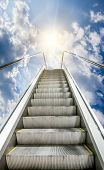 The Escalator Is Moving Up To The Blue Sky With The Sun