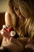 foto of whipping  - Sexy woman feeding man with strawberry with whipped cream