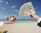 stock photo of sand dollar  - hand giving money for travel on a beach background - JPG