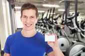 foto of visitation  - Young Healthy Athletic Man Holding Blank Visiting Card At Gym - JPG