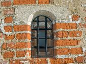 Small barred window in an old brick wall