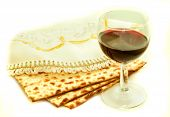 picture of hebrew  - the symbols of the feast of Passover three pieces of matzah poured a glass of red wine white cloth with embroidery and font on the Hebrew Pesach on a white background isolated - JPG