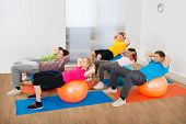 picture of pilates  - Group Of Multiethnic People Exercising On Pilate Ball At Gym - JPG