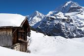 Old farmhouse in front of the Jungfrau in the Winter