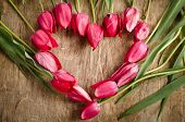 The Heart-shaped Frame Of Fresh Tulips Is Laying On An Old Rustic Wooden Background