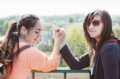 Постер, плакат: Girls engaged in arm wrestling